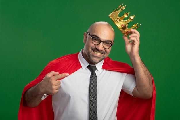 Super eroe uomo d'affari in mantello rosso e occhiali che indossa la corona guardando fiducioso pointign sorridente con il dito indice alla corona in piedi sopra la parete verde