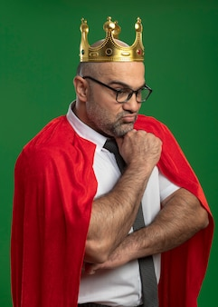 Super hero businessman in red cape and glasses wearing crown looking down with hand on chin with confident serious expression thinking