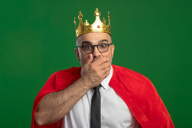Super hero businessman in red cape and glasses wearing crown looking at front being amazed and surprised covering mouth with hand standing over green wall