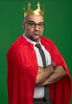 Uomo d'affari super eroe in mantello rosso e occhiali che indossa la corona guardando davanti sentendosi orgoglioso auto-soddisfatto con le braccia incrociate sul petto in piedi sopra la parete verde