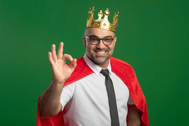 Super eroe uomo d'affari in mantello rosso e occhiali che indossa la corona guardando davanti sorridendo allegramente mostrando segno giusto in piedi verde muro bianco