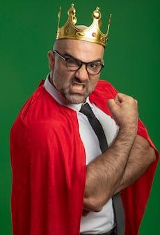 Super eroe uomo d'affari in mantello rosso e occhiali che indossa la corona guardando davanti con grave faccia accigliata che stringe il pugno che mostra la forza in piedi sopra la parete verde