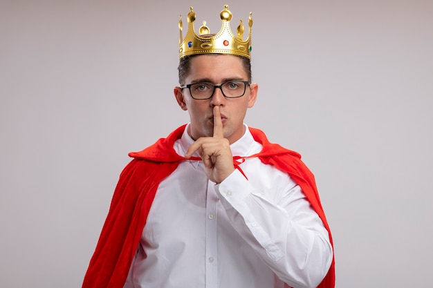 Super hero businessman in red cape and glasses wearing crown making silence gesture with finger on lips standing over white wall