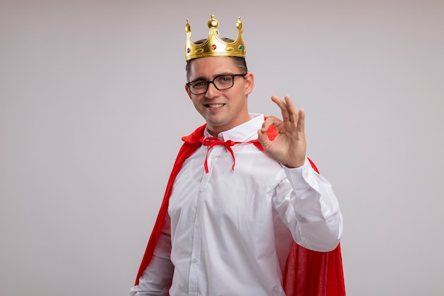 Super hero businessman in red cape and glasses wearing crown  smiling cheerfully showing ok sign standing over white wall