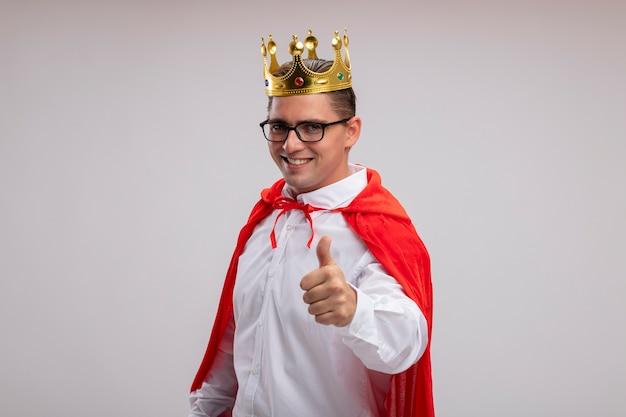 Uomo d'affari super eroe in mantello rosso e occhiali che indossano corona sorridente con la faccia felice che mostra i pollici in su in piedi sul muro bianco