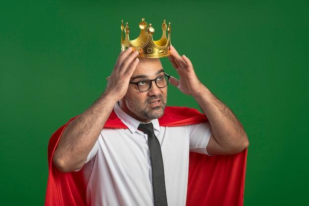 Uomo d'affari super eroe in mantello rosso e occhiali che indossano corona toccandolo loking fiducioso in piedi sopra la parete verde