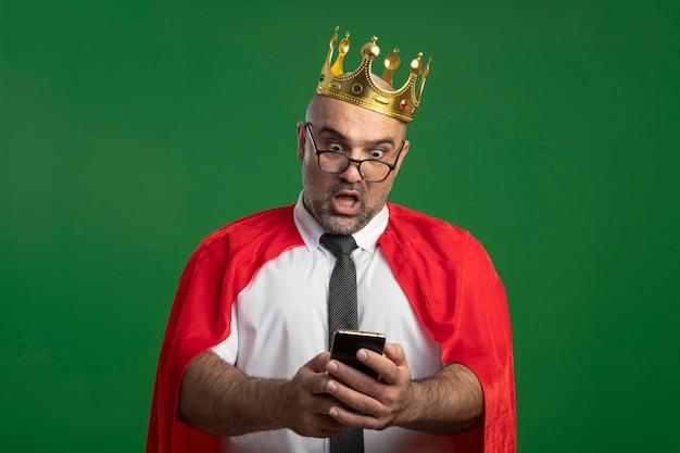 Uomo d'affari super eroe in mantello rosso e occhiali che indossa la corona utilizzando smartphone che sembra confuso e sorpreso