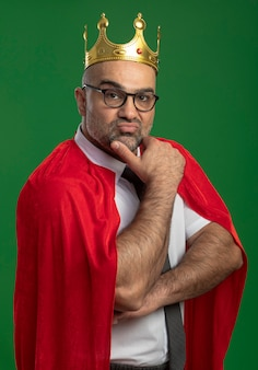 Super hero businessman in red cape and glasses wearing crown with hand on chin with confident serious expression