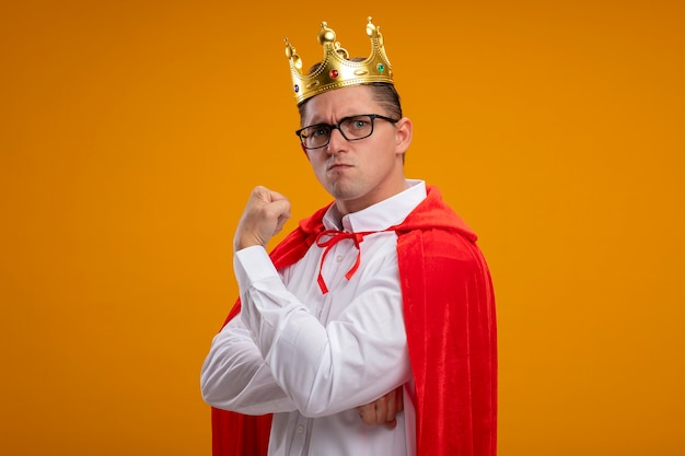 Super hero businessman in red cape and glasses wearing crown  with serious frowning face clenching fist showing strength standing over orange wall