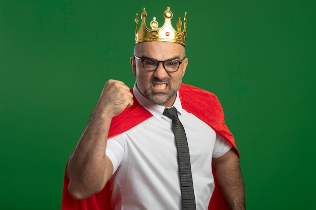 Super eroe uomo d'affari in mantello rosso e occhiali che indossa la corona con grave faccia accigliata che stringe il pugno mostrando forza