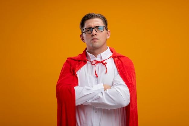 Uomo d'affari super eroe in mantello rosso e occhiali con la faccia seria con le mani incrociate sul petto in piedi sopra la parete arancione