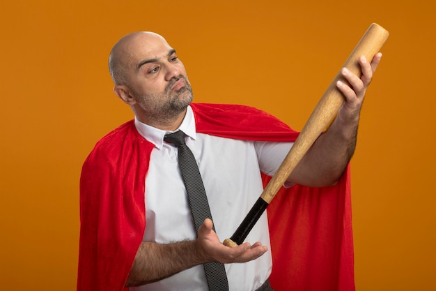 Super hero businessman in red cape holding baseball bat looking at it intrigued