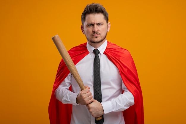 Uomo d'affari super eroe in mantello rosso che tiene la mazza da baseball con il viso serio accigliato in piedi sopra la parete arancione