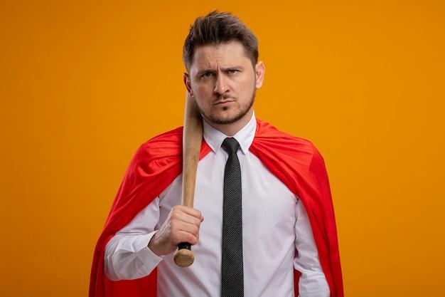 Uomo d'affari super eroe in mantello rosso che tiene la mazza da baseball con la faccia seria in piedi sopra la parete arancione