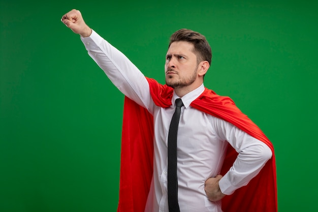 Super hero businessman in red cape holding crown keeping arm in flying gesture ready to fight standing over green background