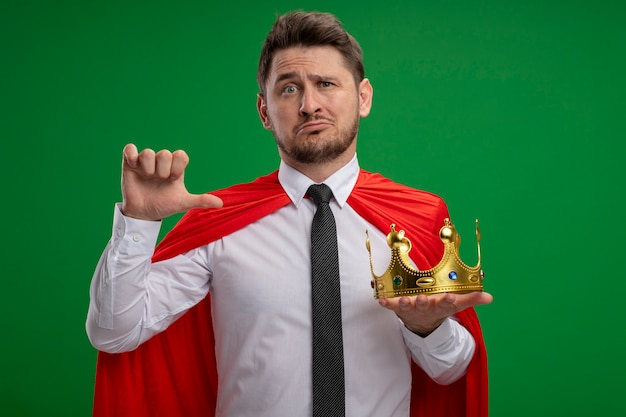Super hero businessman in red cape holding crown pointing at it being confused standing over green background
