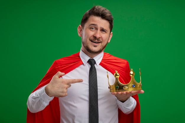 Super hero businessman in red cape holding crown pointing with index finger at it smiling with happy face standing over green background