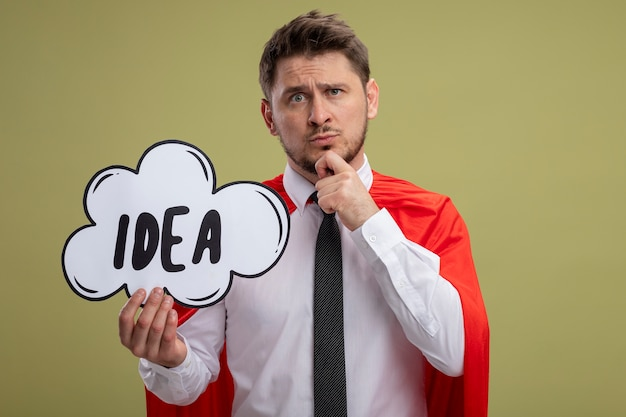 Super hero businessman in red cape holding speech bubble sign with word idea looking puzzled standing over green background