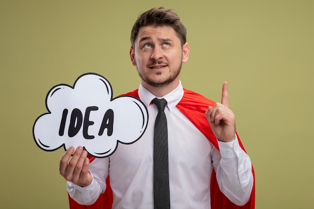 Super hero businessman in red cape holding speech bubble sign with word idea looking up showing index finger having new idea standing over green background