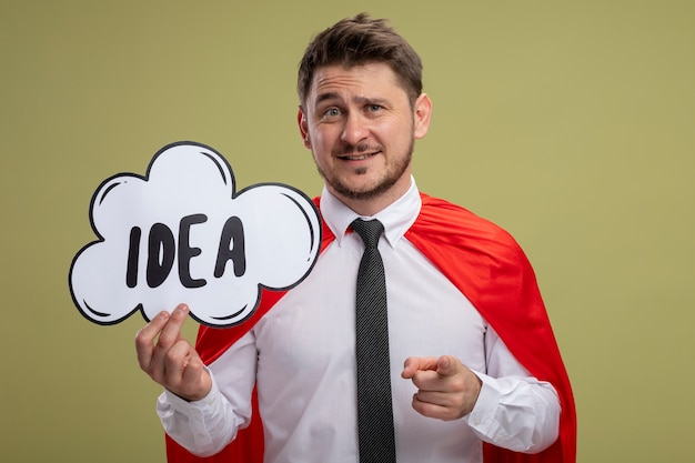 Super hero businessman in red cape holding speech bubble sign with word idea pointing with index finger at camera smiling standing over green background