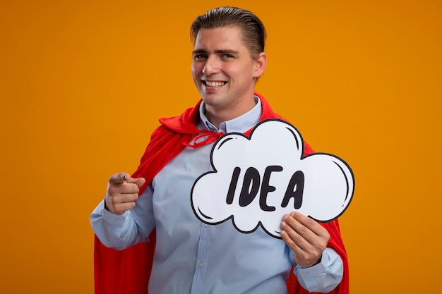 Super hero businessman in red cape holding speech bubble sign with word idea pointing with index finger at camera smiling standing over orange background