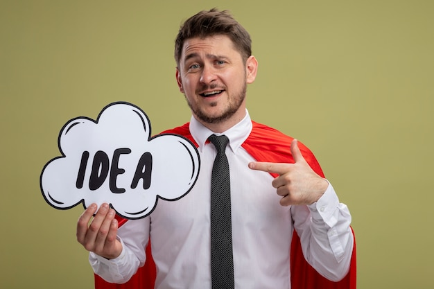 Super hero businessman in red cape holding speech bubble sign with word idea pointing with index finger at it smiling standing over green background