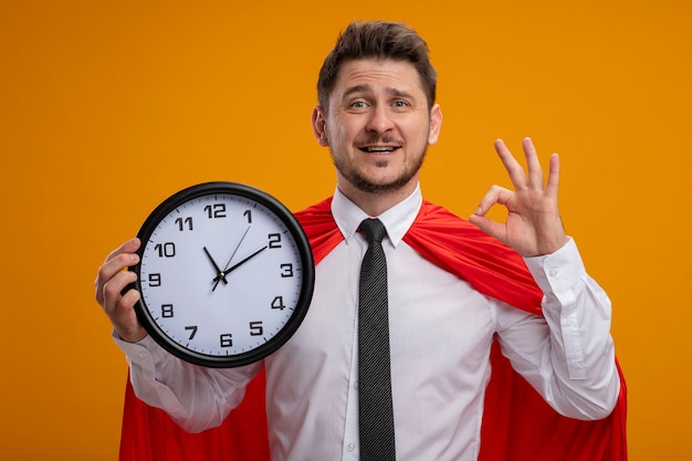 Super hero businessman in red cape holding wall clock looking at camera smiling cheerfully showing ok sign standing over orange background
