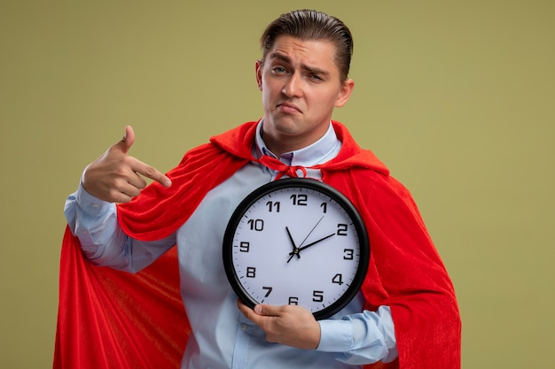 Super hero businessman in red cape holding wall clock looking confident and being pleased pointing with index finger at clock standing over light background