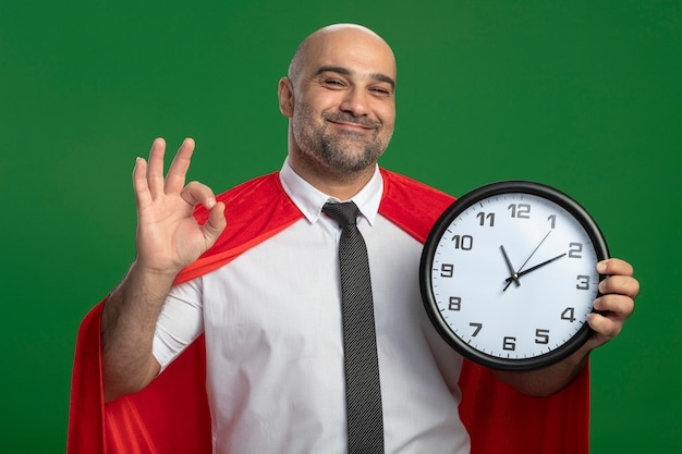 Uomo d'affari super eroe in mantello rosso che tiene orologio da parete guardando davanti sorridendo allegramente mostrando segno giusto in piedi sopra la parete verde