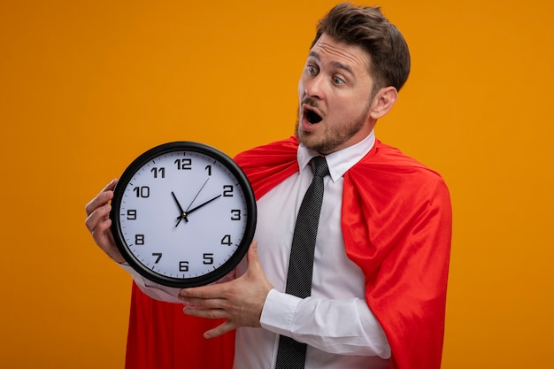 Super hero businessman in red cape holding wall clock looking at it being amazed and surprised standing over orange wall