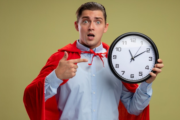 Super hero businessman in red cape holding wall clock pointign with index figner at it being surprised standing over light background