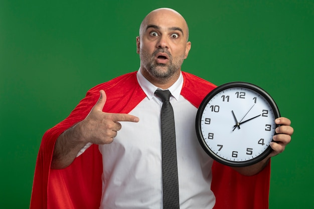 Super hero businessman in red cape holding wall clock pointing with index finger at it being amazed and surprised standing over green wall