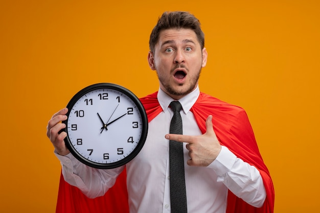 Super hero businessman in red cape holding wall clock pointing with index finger at it being amazed and surprised standing over orange wall