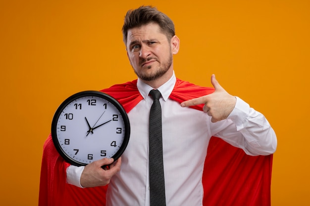 Super hero businessman in red cape holding wall clock pointing with index finger at it looking confused standing over orange wall