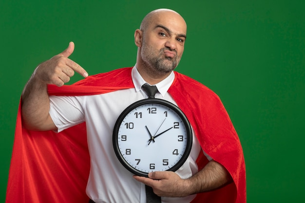 Super hero businessman in red cape holding wall clock pointing with index finger at it with skeptic expression on face standing over green wall