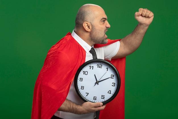 Uomo d'affari super eroe in mantello rosso che tiene l'orologio da parete che grida con il pugno chiuso con espressione arrabbiata in piedi sopra la parete verde