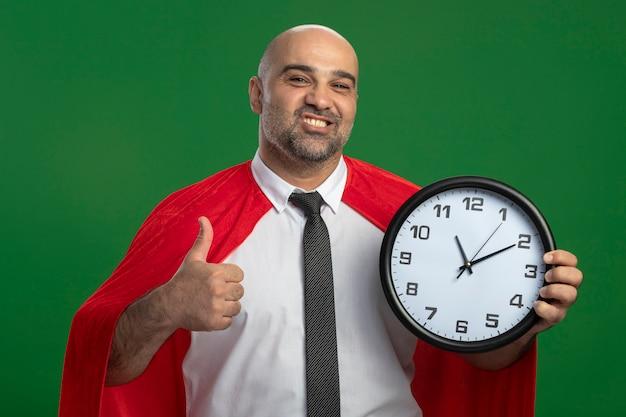Uomo d'affari super eroe in mantello rosso che tiene orologio da parete, sorridendo allegramente mostrando i pollici in piedi sopra la parete verde