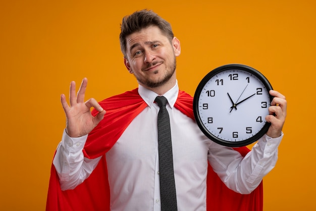 Super hero businessman in red cape holding wall clock  smiling showing ok sign standing over orange wall