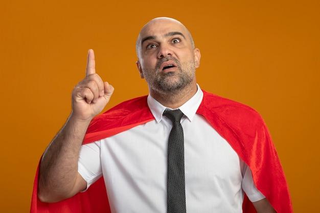 Uomo d'affari del super eroe in mantello rosso che cerca mostrando il figner indice che è sorpreso di avere una nuova idea