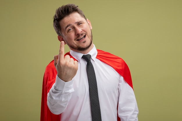 Super hero businessman in red cape lookign at camera smiling showing index finger standing over green background