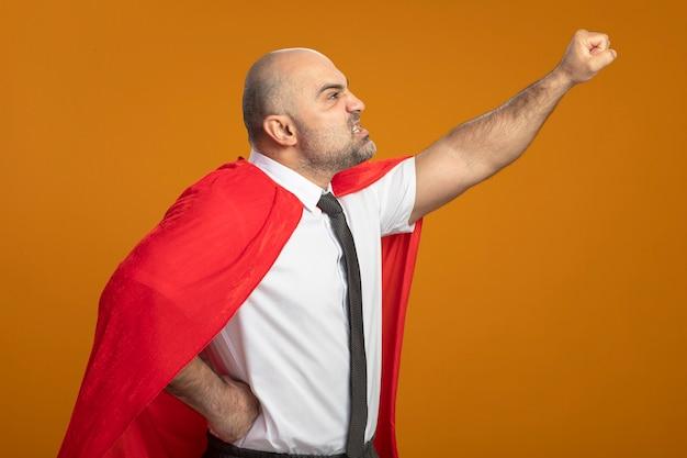 Uomo d'affari super eroe in mantello rosso che osserva da parte con la faccia arrabbiata che fa il gesto vincente pronto a combattere in piedi sopra il muro arancione