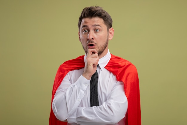 Super hero businessman in red cape looking aside with hand on chin thinking being surprised standing over green background