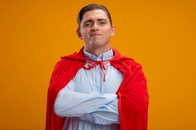 Super hero businessman in red cape looking at camera with smile on face with crossed arms on chest standing over orange background
