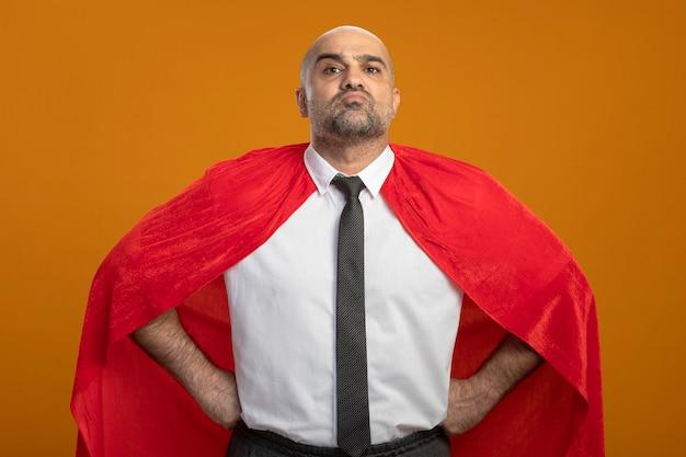 Uomo d'affari super eroe in mantello rosso che sembra fiducioso con le braccia all'anca in piedi sopra la parete arancione