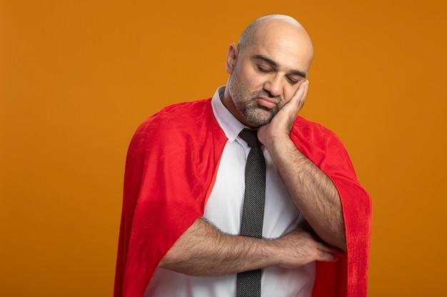Uomo d'affari super eroe in mantello rosso guardando davanti con espressione triste che si appoggia la testa sul palmo in piedi stanco e annoiato sopra la parete arancione