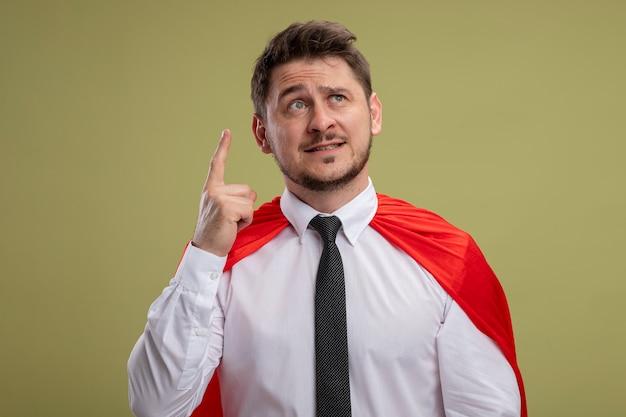 Uomo d'affari super eroe in mantello rosso che osserva in su dito indice mostrando emotivo avendo grande idea in piedi sopra la parete verde
