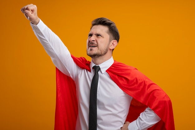 Super hero businessman in red cape looking up making winning gesture ready to help standing over orange background