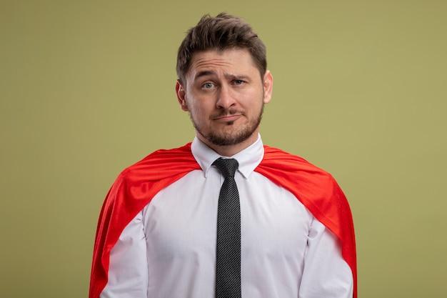 Uomo d'affari super eroe in mantello rosso guardando con espressione triste in piedi sopra la parete verde