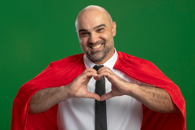 Uomo d'affari super eroe in mantello rosso che fa il gesto del cuore con le dita guardando la parte anteriore sorridendo allegramente in piedi sopra la parete verde