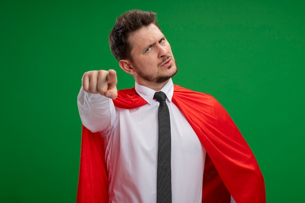 Super hero businessman in red cape pointing with index figner at camera being displeased standing over green background